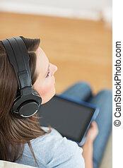 Mujer escuchando música con su tabla digital en el sofá