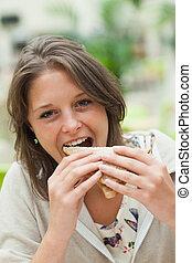 Mujer estudiante comiendo sándwich en la cafetería