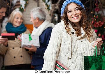 Mujer feliz con familia en la tienda de Navidad