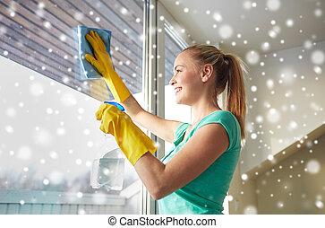 Mujer feliz con guantes limpiando ventana con trapo