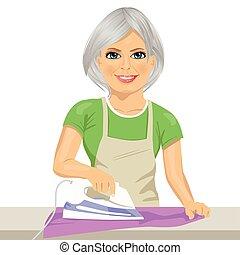 Mujer feliz de último año planchando ropa. Trabajo doméstico
