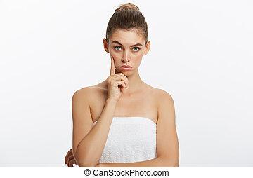 Mujer feliz del spa pensando en buscar aislada en el fondo blanco. Hermosa caucásica sonriente con toallas.