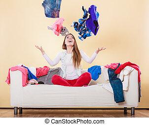 Mujer feliz en el sofá en una habitación desordenada tirando ropa