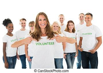 Mujer feliz mostrando texto voluntario en camiseta