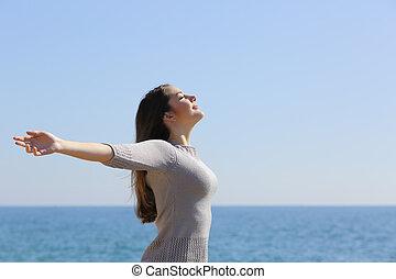 Mujer feliz respirando aire fresco y levantando brazos en la playa