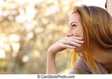 Mujer feliz riendo cubriéndose la boca con una mano