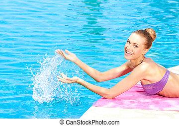 Mujer feliz salpicando agua en la piscina
