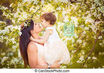 Mujer feliz y niño en el maldito jardín de primavera. Una mujer besándose. El concepto de las fiestas de las madres