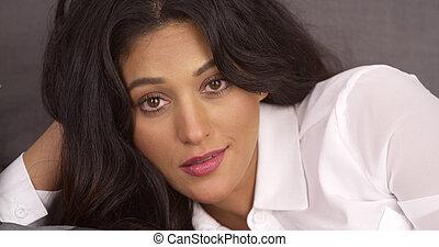 Mujer hispana atractiva tendida en el sofá