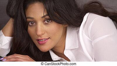 Mujer hispana sexy tumbada en el sofá y mirando a la cámara