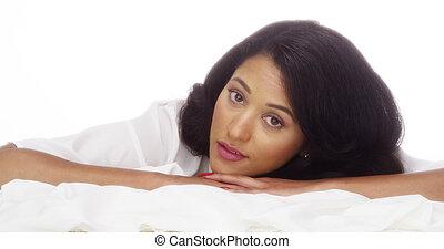 Mujer hispana tendida en la cama
