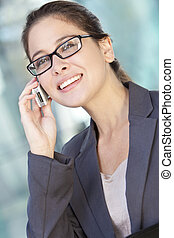 Mujer inteligente de negocios con traje y hablando por celular