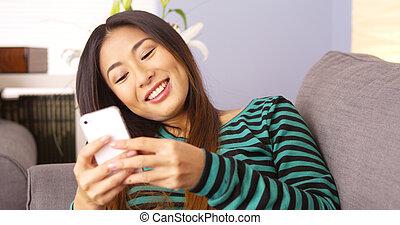 Mujer japonesa feliz enviando mensajes en smartphone