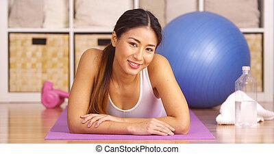 Mujer japonesa feliz tumbada en el tapete de yoga