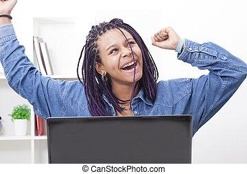 Mujer joven celebrando el éxito con la computadora portátil