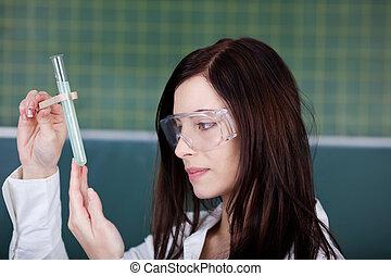Mujer joven comprobando una reacción química
