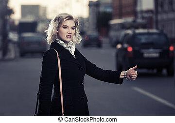 Mujer joven de la moda llamando a un taxi en la calle City