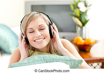 mujer, joven, encantado, escuchar, música, sofá, acostado