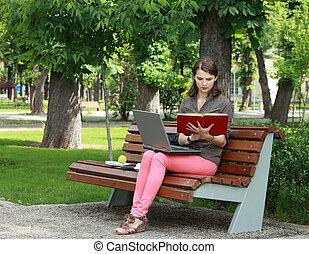 Mujer joven estudiando en un parque