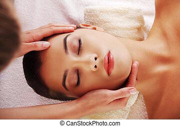 Mujer joven masaje facial en el spa