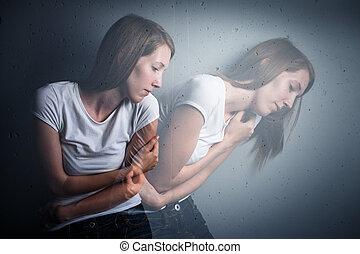 Mujer joven que sufre de una depresión severa / ansiedad (imagen tonificada de color; técnica de doble exposición se utiliza para transmitir el estado de ánimo de la enfermedad, la progresión de la ansiedad/depresión)