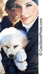 Mujer joven sosteniendo cachorro