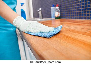 Mujer limpiando la encimera de la cocina
