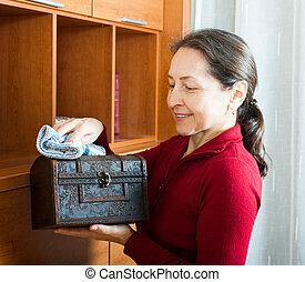 Mujer madura limpiando polvo de pecho de madera