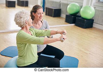 Mujer mayor asistida por entrenador personal en el gimnasio