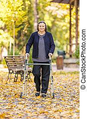 Mujer mayor caminando al aire libre con Walker en el parque de otoño