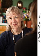 Mujer mayor en la cocina con hija o amiga