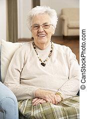 Mujer mayor en la silla de casa