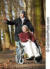 Mujer mayor en silla de ruedas caminando con su hijo