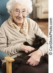 Mujer mayor relajándose en la silla con gato mascota
