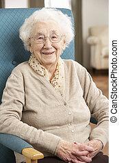 Mujer mayor relajada en la silla de casa