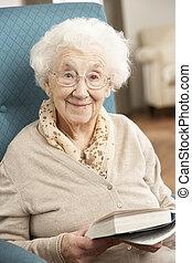 Mujer mayor relajada en la silla en el libro de lectura