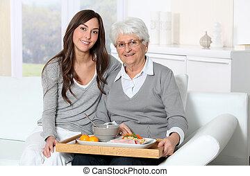 Mujer mayor y cuidadora sentada en el sofá con bandeja de almuerzo