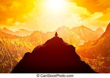 Mujer meditando en posición de yoga sentada en la cima de una montaña sobre nubes al atardecer.