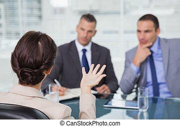 Mujer morena hablando con sus entrevistadores