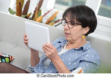 Mujer morena madura sentada en el sofá usando tablet digital