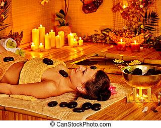 Mujer recibiendo masaje de piedra.