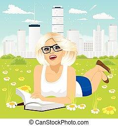 Mujer recostada en el libro de lectura de hierba