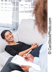 Mujer riéndose en sofá durante la sesión de terapia