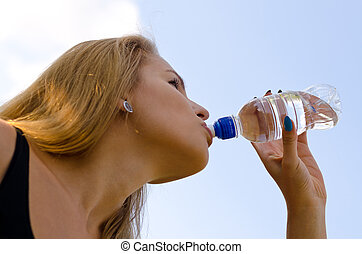 Mujer rubia bebiendo agua embotellada