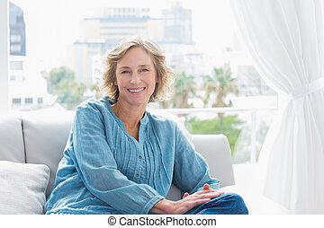 Mujer rubia contenida sentada en su sofá