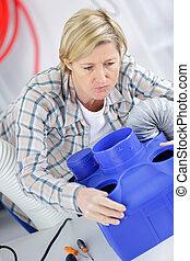 Mujer rubia instalando un nuevo sistema de aire acondicionado