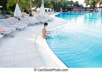 Mujer salpicando agua en la piscina