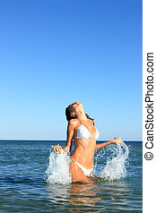 Mujer salpicando en agua tropical