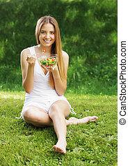 Mujer sana comiendo ensalada
