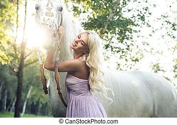 Mujer satisfecha abrazando a caballo blanco